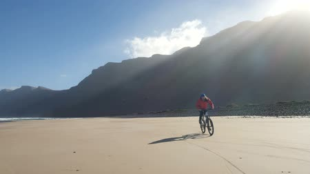 waterline : Young man rides a bicycle on a sand beach on Canary Islands towards waves of Atlantic ocean. Lanzarote