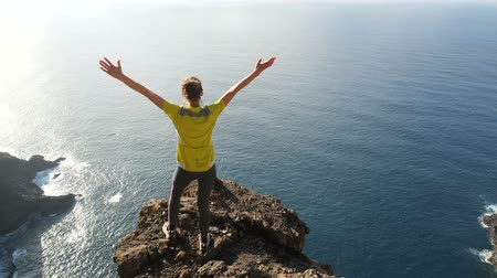 gözcü : Young woman raising her arms on beautiful steep cliff over the ocean. Lady on the summit in beautiful scenery.