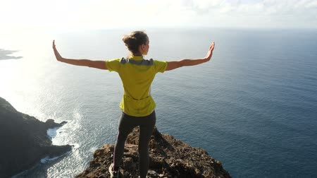 günışınları : Young woman raising her arms on beautiful steep cliff over the ocean. Lady on the summit in beautiful scenery.