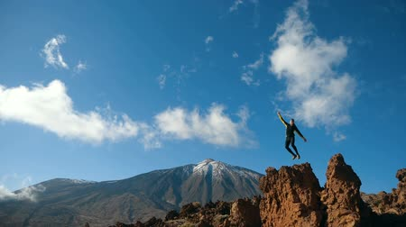 erupção : Man jumps on a big stone in slow motion. Teide volcano on the background, Tenerife, Canary islands, Spain.