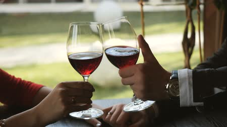 kırmızı şarap : Close up of loving couple holding hands and clinking glasses of red wine during romantic dinner