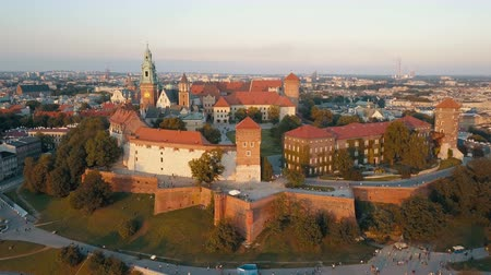 fortress : Aerial view of Royal Wawel Cathedral and castle in Krakow, Poland, with Vistula river, park, yard and tourists at sunset. Old city in the background Stock Footage