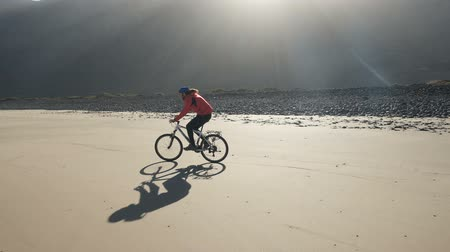 waterline : Young man rides a bicycle on a sand beach on Canary Islands. Wheelie trick on a sand, Lanzarote, Atlantic ocean Stock Footage