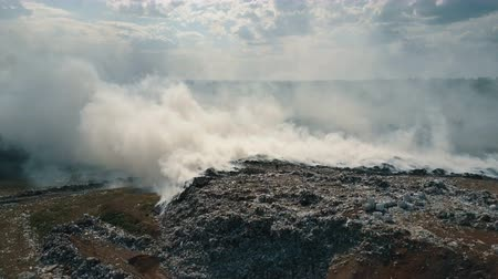 Aerial view of burning garbage dump polluting the environment. Strong wind rises toxic smoke of burning garbage into the air and spreads it on long distance.