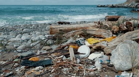 descuidado : Trash, plastic, garbage, environmental pollution on the beach. Waves in slow motion on a background. Trash, plastic bottle on the beach. Waste that pollutes the ocean environment