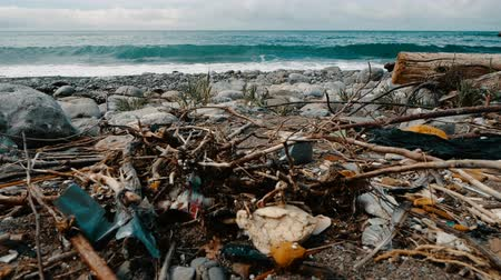 poluir : Trash, plastic, garbage, environmental pollution on the beach. Waves in slow motion on a background. Trash, plastic bottle on the beach. Waste that pollutes the ocean environment