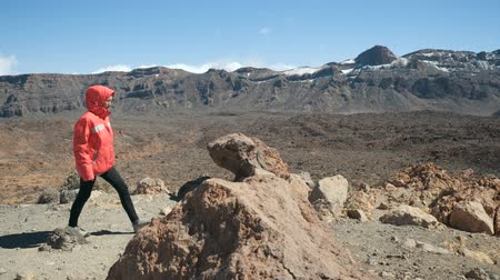 törekvés : Young woman walking high in mountains and observing a huge crater of Teide volcano in Tenerife, Canary islands, Spain.