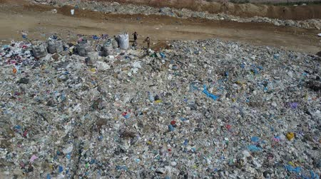 guba : Aerial view of City garbage Dump. Gypsy family with children separates trash to gain some money