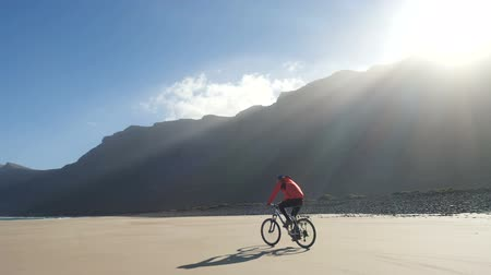 waterrad : Young man rides a bicycle on a sand beach on Canary Islands in beautiful sunrise light against fantastic mountains on Lanzarote island in Atlantic ocean. Slow motion. Stockvideo