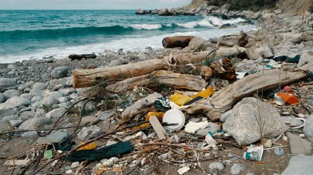descuidado : Trash, plastic, garbage, environmental pollution on the seashore. Waves in slow motion on a background. Trash, plastic bottle on the beach. Waste that pollutes the ocean environment Stock Footage