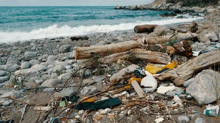 krym : Trash, plastic, garbage, environmental pollution on the seashore. Waves in slow motion on a background. Trash, plastic bottle on the beach. Waste that pollutes the ocean environment Dostupné videozáznamy