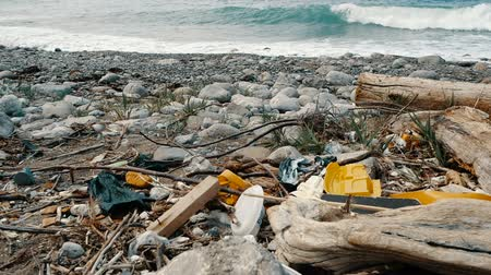 poluir : Trash, plastic, garbage, environmental pollution on the seashore. Waves in slow motion on a background. Trash, plastic bottle on the beach. Waste that pollutes the ocean environment Stock Footage