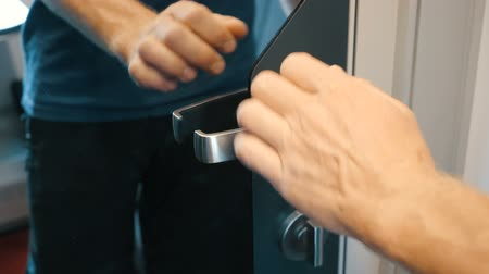 doorway : Mans hand unlocks a latch and opens a mirror door with metal handle. Man exits a modern comfortable train compartment. A train passenger closes a mirror door from outside.