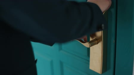 odemknout : Man in dark blue suit tries to unlock a massive turquoise door with a wrong plastic card key. Man can not unlock a door with a plastic card. Close up of a door handle.