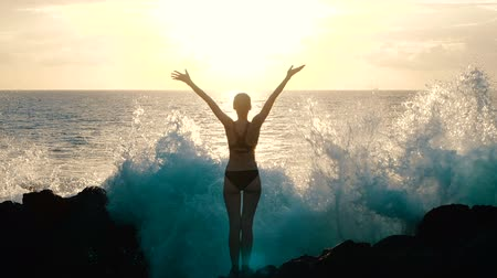Silhouette of a woman at sunset raising arms in the air and observing huge ocean waves crashing on rocks and spraying. Cinematic slow motion