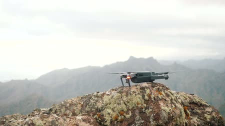 Close up of a consumer drone launching and taking flight off from a rough rock high in Mountains. Slow motion, ground level view Dostupné videozáznamy