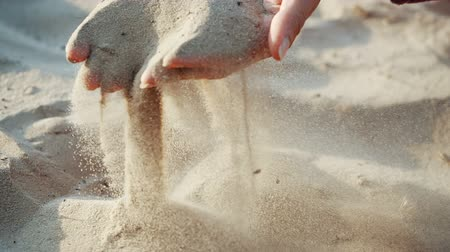 věčnost : SLOW MOTION, CLOSE UP: The sand passes through the fingers of a young woman. The sand is running through fingers of a lady and is spread by a strong wind.