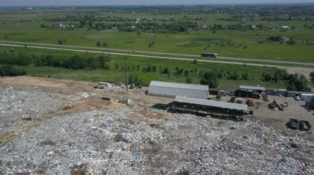 выигрыш : Aerial view of City garbage Dump. Gypsy family with children separates trash to gain some money