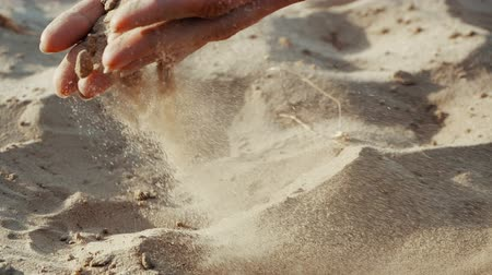 setaccio : SLOW MOTION, CLOSE UP: The sand passes through the fingers of a young woman. The sand is running through fingers of a lady and is spread by a strong wind.
