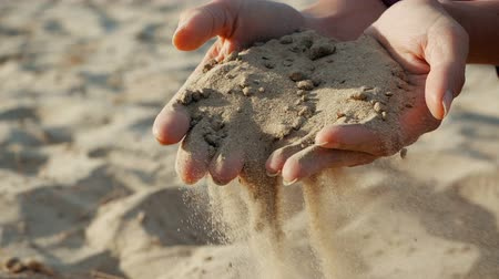 zeef : SLOW MOTION, CLOSE UP: The sand passes through the fingers of a young woman. The sand is running through fingers of a lady and is spread by a strong wind.