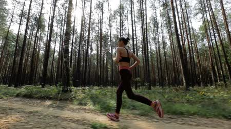 stabilizátor : Happy young woman is jogging in a forest or in a park among trees. Tracking shot with stabilized camera