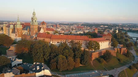 kazimierz : Aerial view of Royal Wawel Cathedral and castle in Krakow, Poland, with Vistula river, park, yard and tourists at sunset. Old city in the background Stock Footage