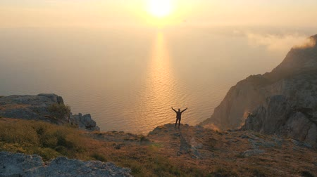 uzanmış : Silhuette of a Young Woman arms outstretched observing a beautiful dramatic sunset above a sea from a high mountain in Crimea.