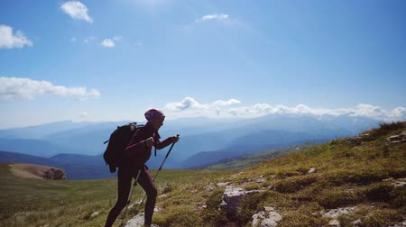 альпинист : Young woman with backpack and trekking poles walks uphill towards the summit. Slow motion. Lady is hiking in beautiful Caucasian mountains.