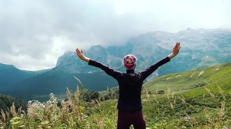 альпинист : Woman hiker raises hands up in mountains enjoying beautiful view and surrounding wild nature. Victory and success, the achievement of the goal.