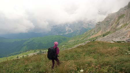 альпинист : Young woman with backpack is hiking in beautiful Caucasian mountains. Lady walks towards the summit.