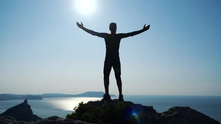 uzanmış : Young long-haired inspired man raises his hands up standing on the top of a mountain above the sea against beautiful blue sky. Silhouette of a happy hiker man standing on the summit. Stok Video