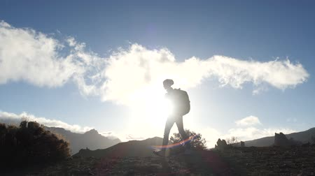 alcançando : Silhouette of a young woman hiker with backpack walking uphill towards the summit against blue sky and clouds at sunset. Slow motion. Lady is hiking in beautiful mountains on Canary Islands. Stock Footage