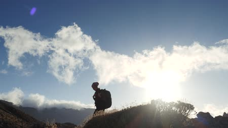 альпинист : Silhouette of a young woman hiker with backpack walking towards the summit against blue sky and clouds. Slow motion. Lady is hiking in beautiful mountains on Canary Islands.