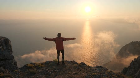 krím : Silhuette of Young man arms outstretched observing beautiful dramatic colorful sunset above a sea from a high mountain in Crimea.