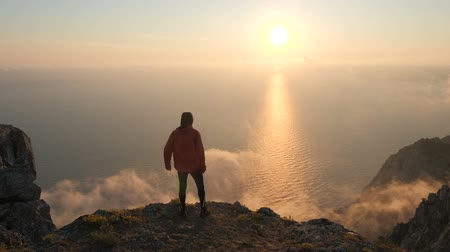 quiet evening : Silhuette of Young man arms outstretched observing beautiful dramatic colorful sunset above a sea from a high mountain in Crimea.