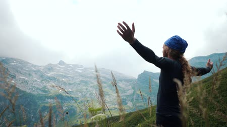 альпинист : Man hiker with long hair raises hands up in mountains enjoying beautiful view and surrounding wild nature. Victory and success, the achievement of the goal.