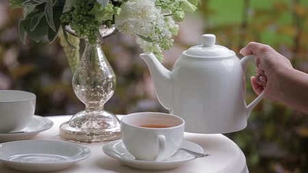 pitcher : Female hand is Pouring hot tea into a white cup. Close up. Filling tea cup served on a white table decorated with a bouquet of flowers.