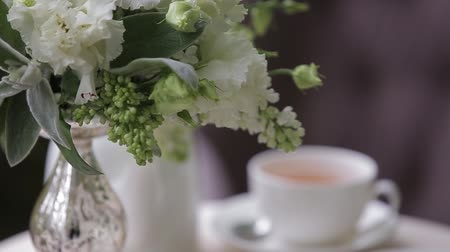 nakrycie stołu : Hot tea in white cups served on a white table decorated with a bouquet of flowers. Focus panorama. Wideo