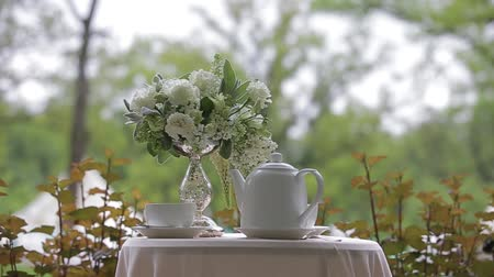 teacup : Hot tea in white cups and white teapot served outdoors on a white table decorated with a bouquet of beautiful flowers.