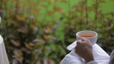 girl in robe : Beautiful young brunette woman in bathrobe drinking tea and relaxing on a terrace. Hot tea in white cups and white teapot served outdoors on a white table decorated with a bouquet of flowers. Stock Footage