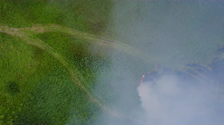 arson : Flight through a smoke from burning green field, wild fire in nature landscape, aerial footage from drone