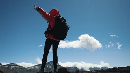 альпинист : Young woman hiker with black backpack arms outstretched stays on the summit high in Mountains against blue sky and clouds. Slow motion. Lady hiker enjoys beautiful mountain scenery on Canary Islands.
