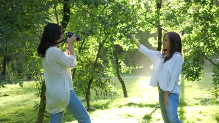 photoshoot : Pretty girl professional photographer wearing white shirt is making photos of a girl in a park on a soft background of green foliage and spraying water. Stock Footage