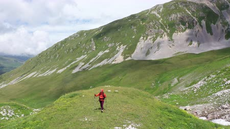 georgien : Aerial view of young Woman with backpack and trekking poles on a mountain route among alpine meadows and rocky cliffs of Adygea. Amazing mountain landscape, Beautiful clouds covering high mountains.