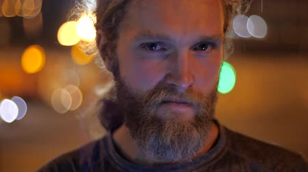 intruder : Close up, Portrait of a handsome Caucasian bearded long-haired young man with envious, evil, angry face. Intruder Man looks straight to the camera on the background of moving evening lights of a city.