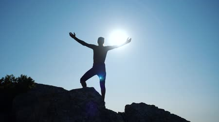 elevação : Young long-haired inspired man raises his hands up standing on the top of a mountain above the sea against beautiful blue sky. Silhouette of a happy hiker man standing on the summit. Stock Footage