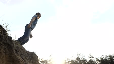 jump away : Young long-haired man jumps in a sand from a cliff in slow motion outdoors at sunset. Stock Footage