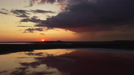 água salgada : Aerial drone shot of a salt lake in Crimea at dramatic sunset. Stunning sunrise over salt Koyashsky lake. flat landscape with mountain on horizon. rain falling from a cloud on the background.