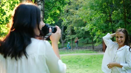 fotoğrafçı : Pretty girl professional photographer wearing white shirt is making photos of a happy smiling girl in a park on a soft background of green foliage and spraying water. Stok Video