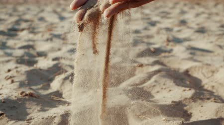 deslizamento : SLOW MOTION, CLOSE UP: The sand passes through the fingers of a young woman. The sand is running through fingers of a lady and is spread by a strong wind.